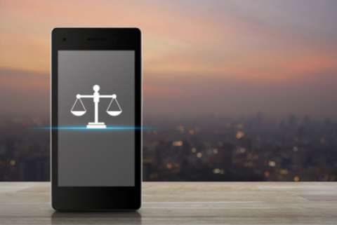a smartphone displaying a glyph of the scales of justice with a cityscape at sunset in the background