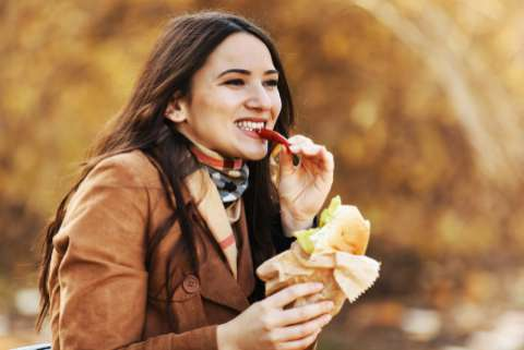 Woman eating sandwich outdoors