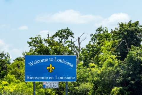 a roadside sign welcoming people to Louisiana, in English and French