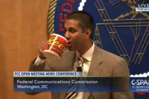 FCC Chairman Ajit Pai drinks from a large mug with the Reese's peanut butter cup logo