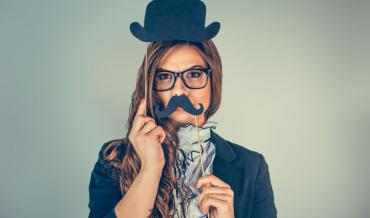 A woman with an obviously fake mustache and fake bowler hat