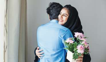 Happy muslim woman getting flowers as a gift from her relative on muslim celebration