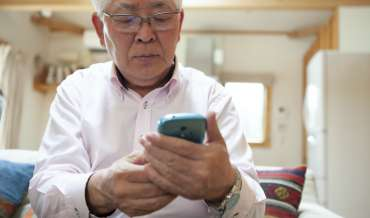 an elderly man looks at his smartphone suspiciously