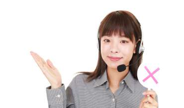 A woman with a headset telephone raises her right palm and holds a sign with a red X in her left hand