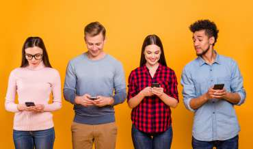 4 people stand in front of an orange wall, looking at their smartphones