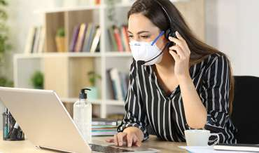 woman wearing mask working from home