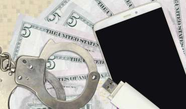 still life with handcuffs, smartphone, flash drive, and five dollar bills (american)