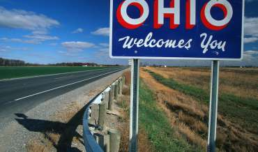 "An ""OHIO Welcomes You"" sign by the side of a highway"