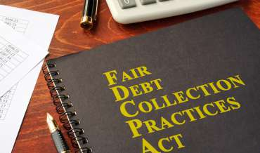 "A notebook that reads ""Fair Debt Collection Practices Act"" sits on a wooden desk next to pens and a calculator"