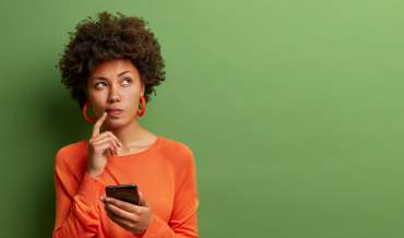 a woman holds a phone and ponders something in front of a green background