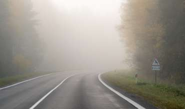A country road stretches into obscuring, white fog