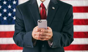 a man in a business suit sends a text message while standing in front of the American flag