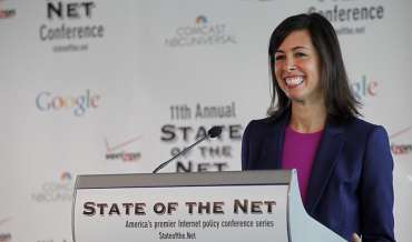 FCC Acting Chair Jessica Rosenworcel smiles while standing at a podium